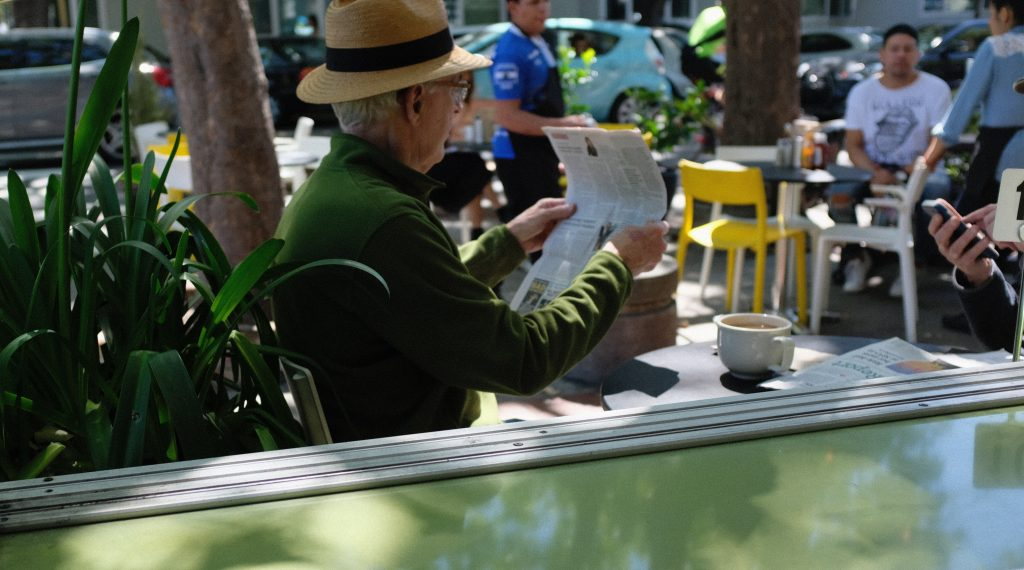 Disfrutando de la sombra en la terraza de un bar leyendo el periódico